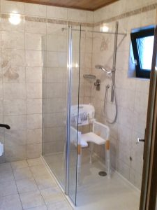 Behindertengerechtes Badzimmer mit Stuhl in der Dusche
